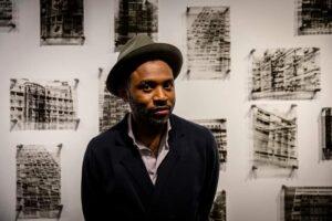 Ritratto di Delio Jasse realizzato in occasione di Foto/Industria 2019 davanti a una parte del suo lavoro Arquivo Urbano, ph courtesy Mistic Media WordPress