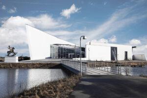 """Vista esterna di ARKEN Museum for Modern Art (sulla sinistra si intravede """"Powerless Structures"""", l'ironica statua equestre di Elmgreen & Dragset che fu esposta per la prima volta nel 2012 a Londra, in Trafalgar Square). Foto Emma Thunbo, courtesy ARKEN Museum for Modern Art"""