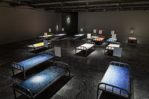 Chen Hui-Chiao, A Room with a View, 2018, mixed mediums (needles, thread, military cots, embroidered towels, basins, toothbrushes, toothpaste, steel cups), 16 pieces, 90 × 200 ×1 40 cm each. Courtesy of the artist and Taipei Fine Arts Museum